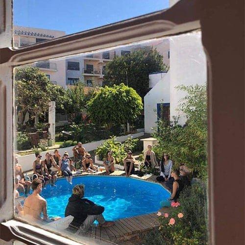 Grupo de pessoas sentadas em torno da piscina do Olive3 num bonito dia de céu azul, avistadas por uma janela no interior do edifício.